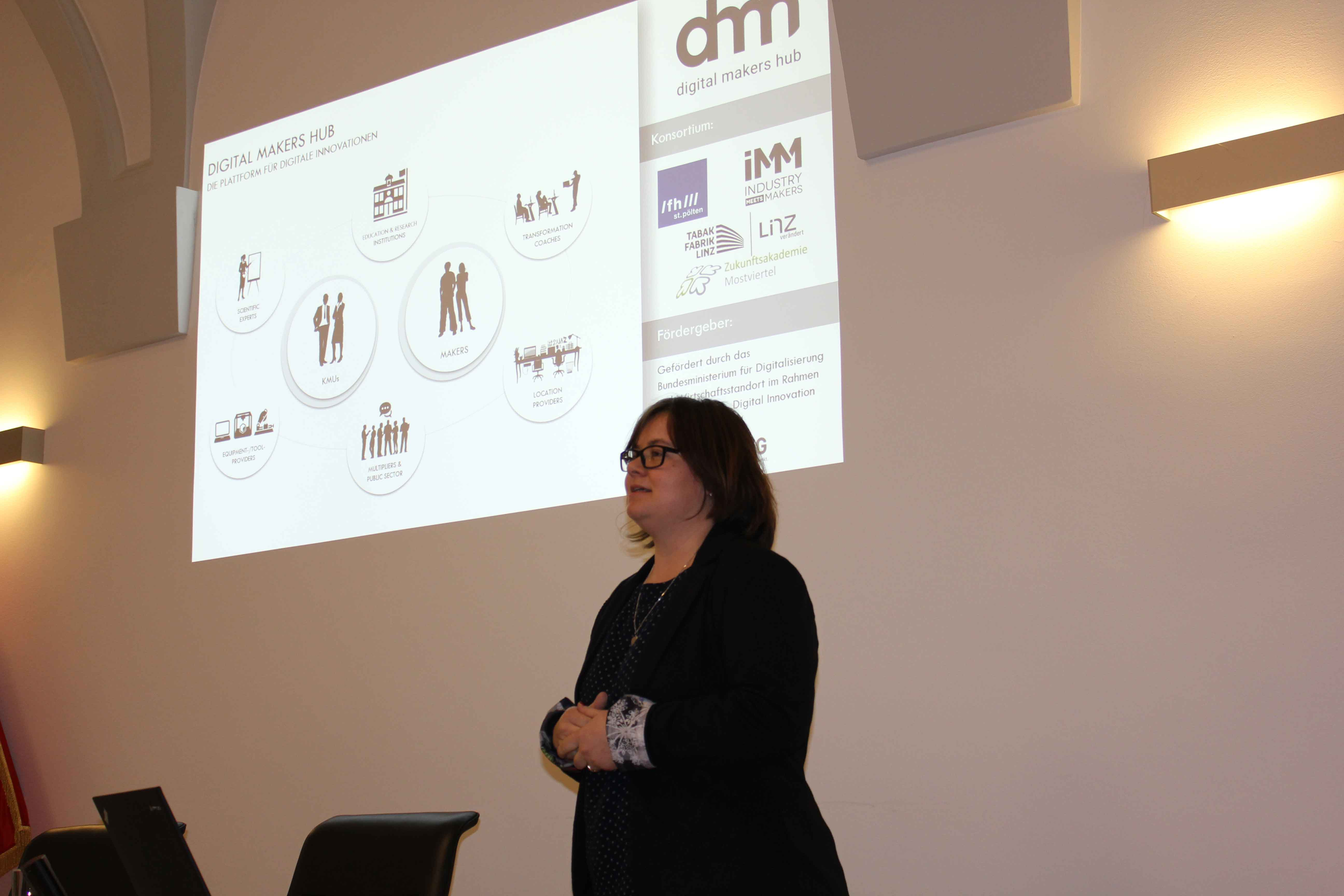 Frau Permoser präsentiert vor einer Leinwand den Digital Makers Hub am SMARTUP Forum