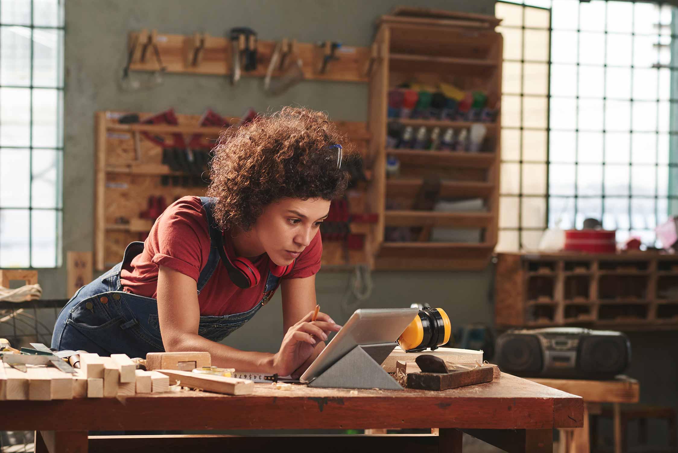 Junges Mädchen steht bei der Werkbank und wirft einen Blick in ihr Tablet.