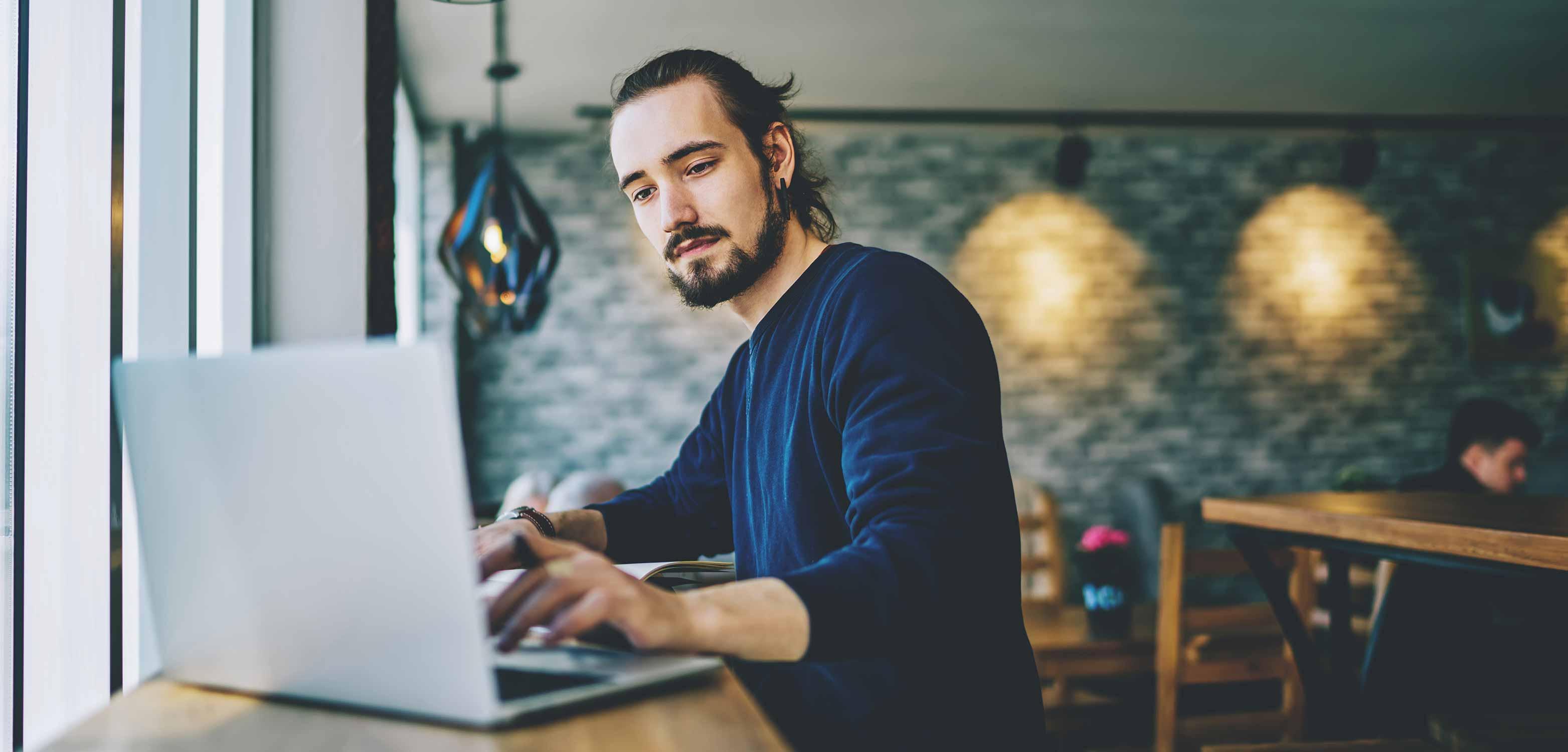 Junger Mann sitzt in einem Kaffeehaus liest die News des Digital Makers Hub