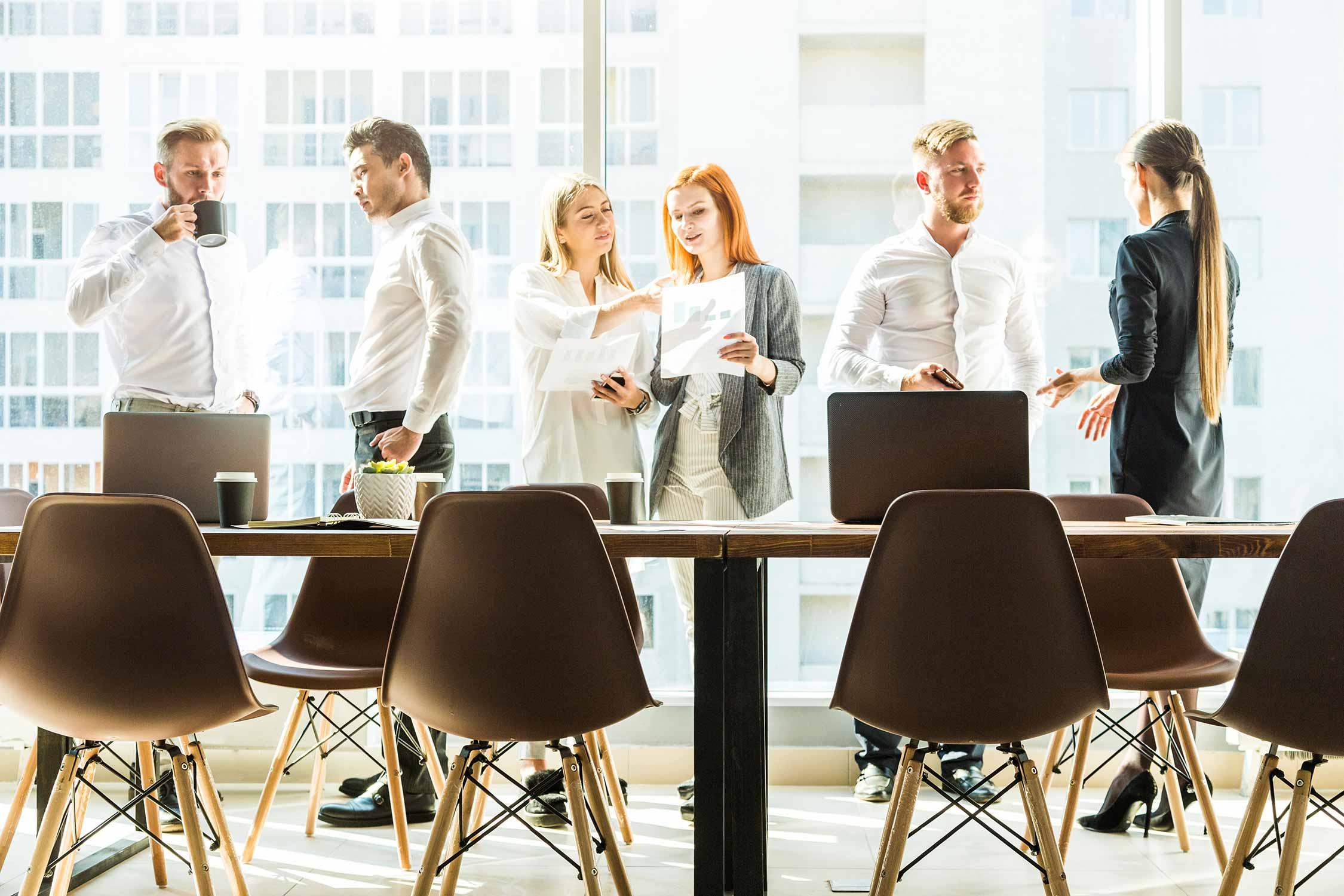 Sechs Personen diskutieren über einen Agendapunkt eines Meetings.