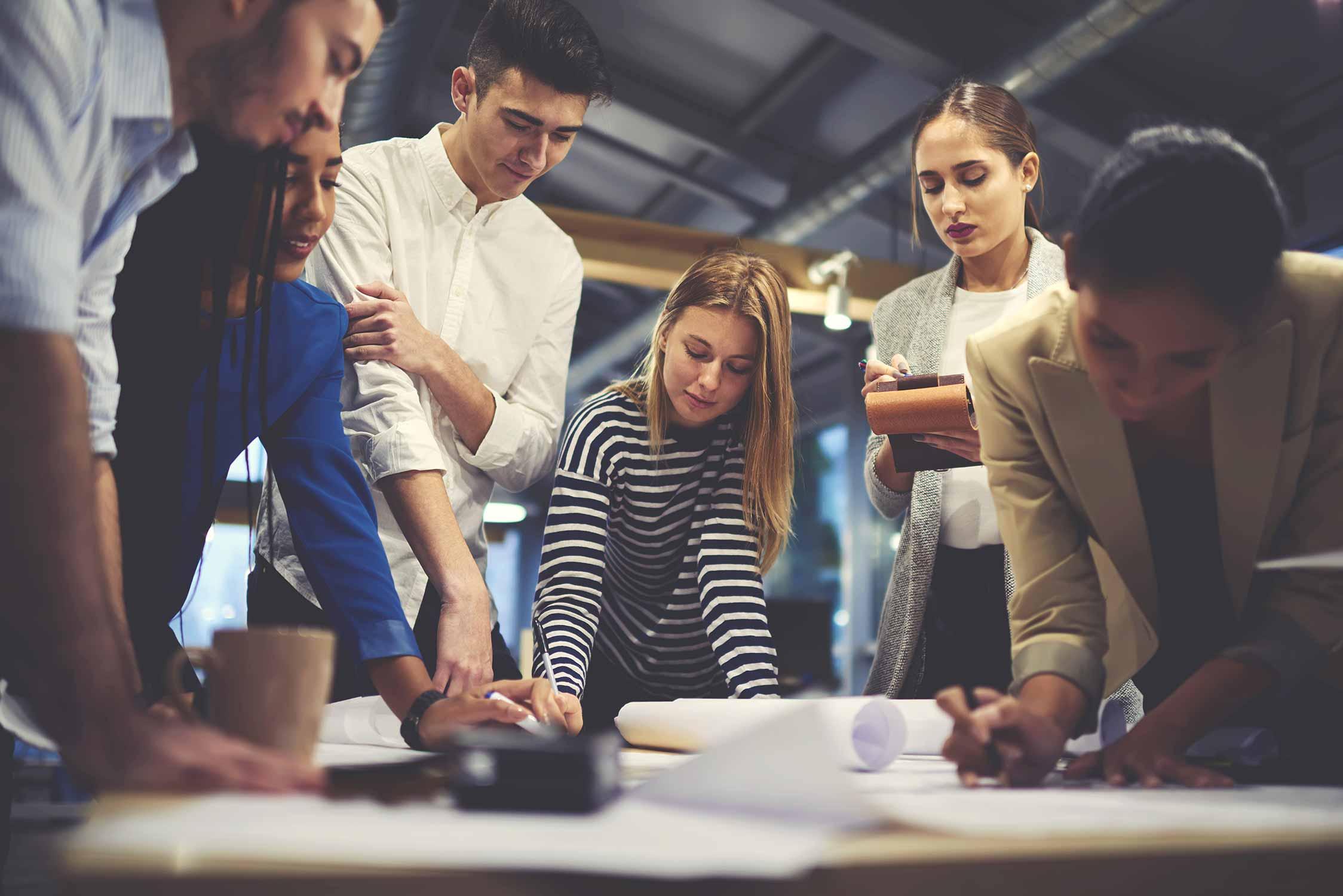Eine Gruppe an Personen steht bei einem Tisch und brainstormed über eine neue, innovative Idee.